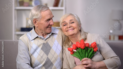 Obraz Elderly couple hugging at home, woman holding bunch of tulips, anniversary gift - fototapety do salonu
