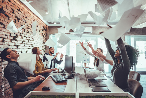 Billede på lærred Smiling business people having fun by throwing papers in the air celebrating business success in the modern office