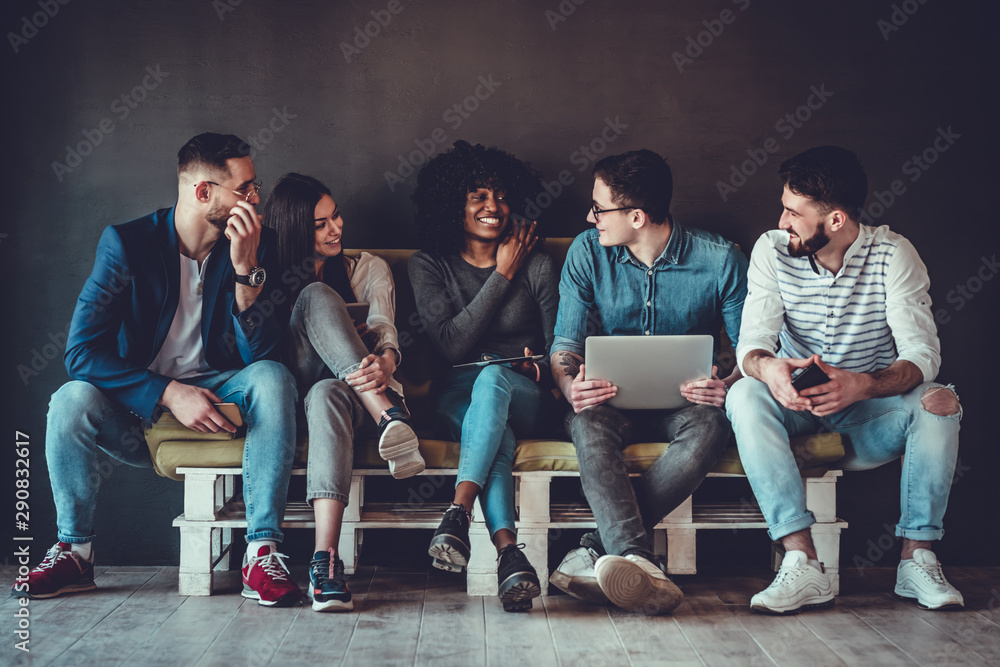 Fototapeta Happy diverse friends group sharing social media app news sitting holding phones, smiling multiracial young people students showing funny videos on laptop
