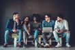 canvas print picture - Multiethnic university students studying together. Young people working with tests and gadgets, sitting on the couch.
