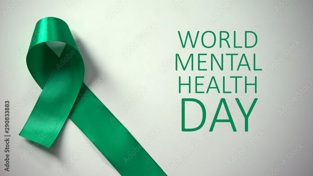Fototapeta World mental health day inscription, green ribbon on table, awareness campaign