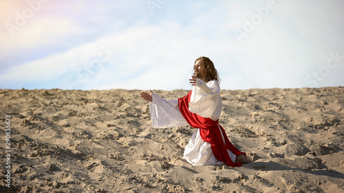 Photo Male pilgrim in white robe kneeing in desert, asking help of Father God, faith