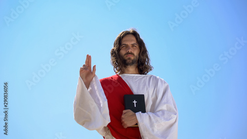 Photo Preacher in robe showing hand of benediction, holding Bible, blessing Christians