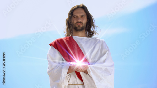 Fotomural  Jesus holding spiritual light against sky, concept of healing, religious miracle