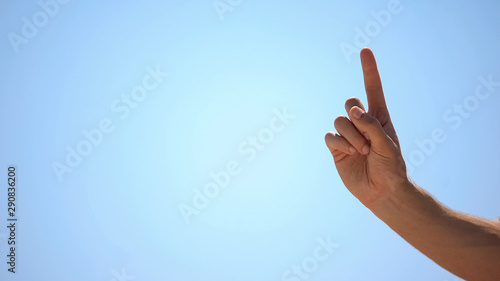 Obraz Male hand pointing finger up on sky background, concept of new idea, wise advice - fototapety do salonu