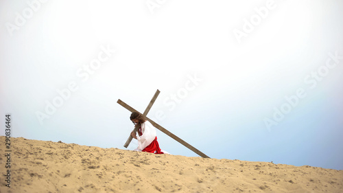 Jesus falling under heavy wooden cross, suffering pain and exhaustion, sacrifice Canvas-taulu