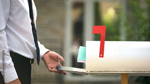 Male sending letters and bills in mailbox in front of house, mail delivery Canvas Print