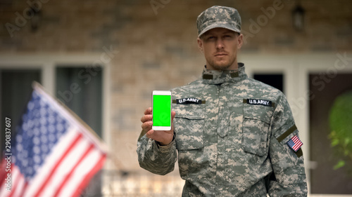 Soldier showing phone with green screen, veterans psychological support online Fototapeta