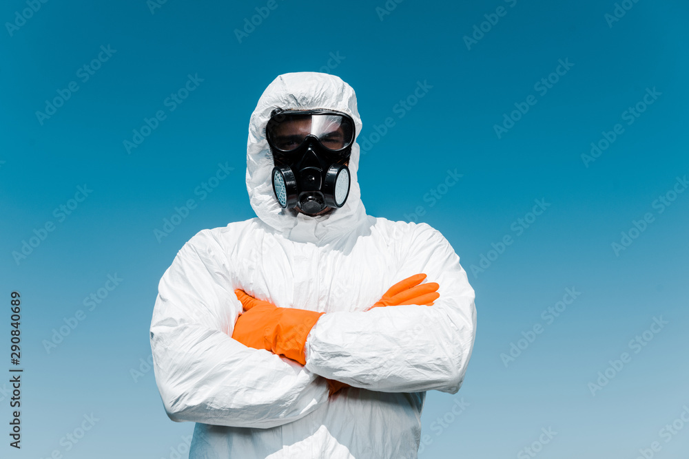 Fototapeta exterminator in protective mask and uniform standing with crossed arms