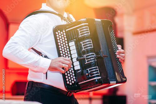 Fényképezés  Adult man plays the button accordion