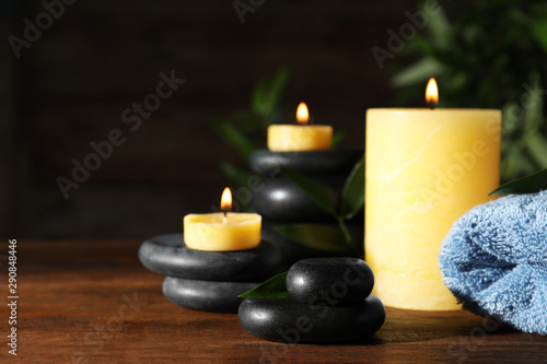 Fototapety, obrazy: Composition with candles and spa stones on wooden table. Space for text