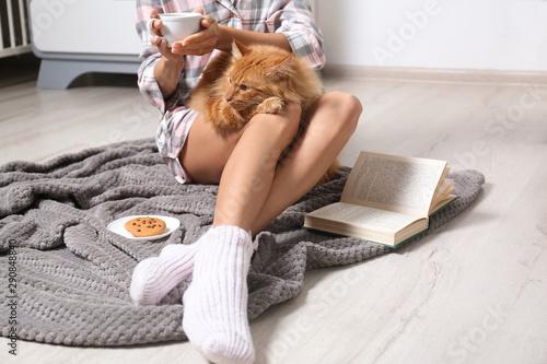 Stampa su Tela  Woman with cute red cat and book on grey blanket at home, closeup view