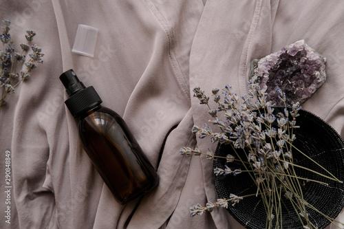 Fototapeta  Glass brown spray bottle with organic cosmetics on gray fabric