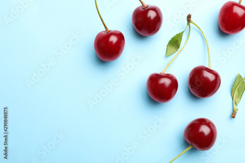 Delicious cherries on blue background, flat lay. Space for text