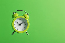 Alarm Clock On Green Backgroun...