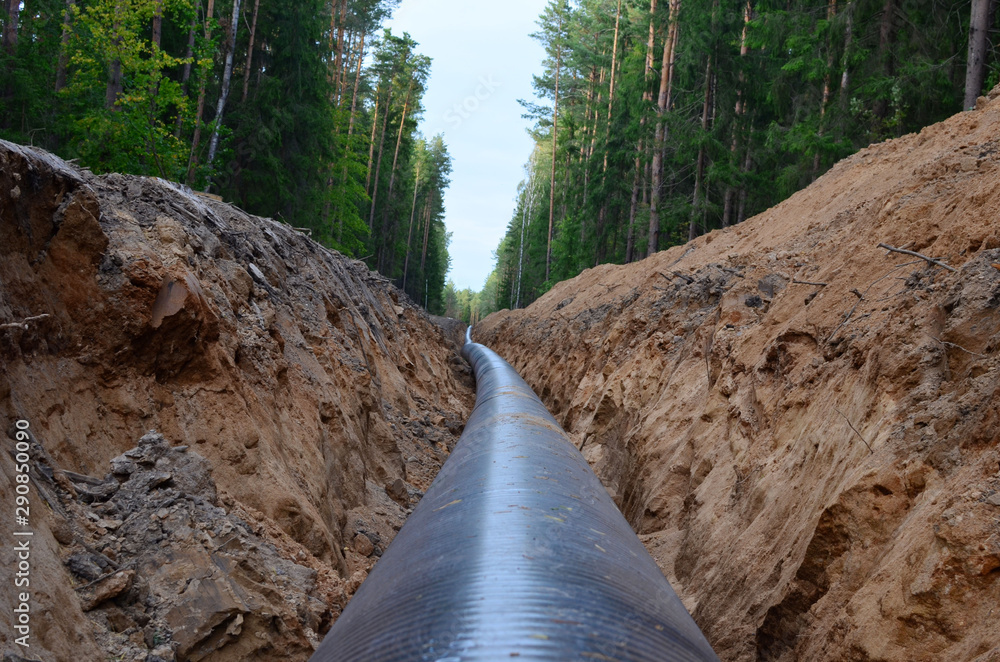 Fototapety, obrazy: Natural gas pipeline construction work. A dug trench in the ground for the installation and installation of industrial gas and oil pipes. Underground work project