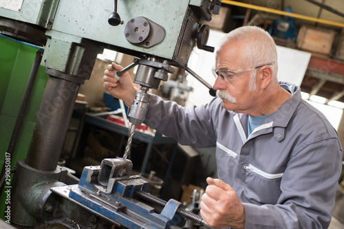 Fotografia  senior worker using bench drill