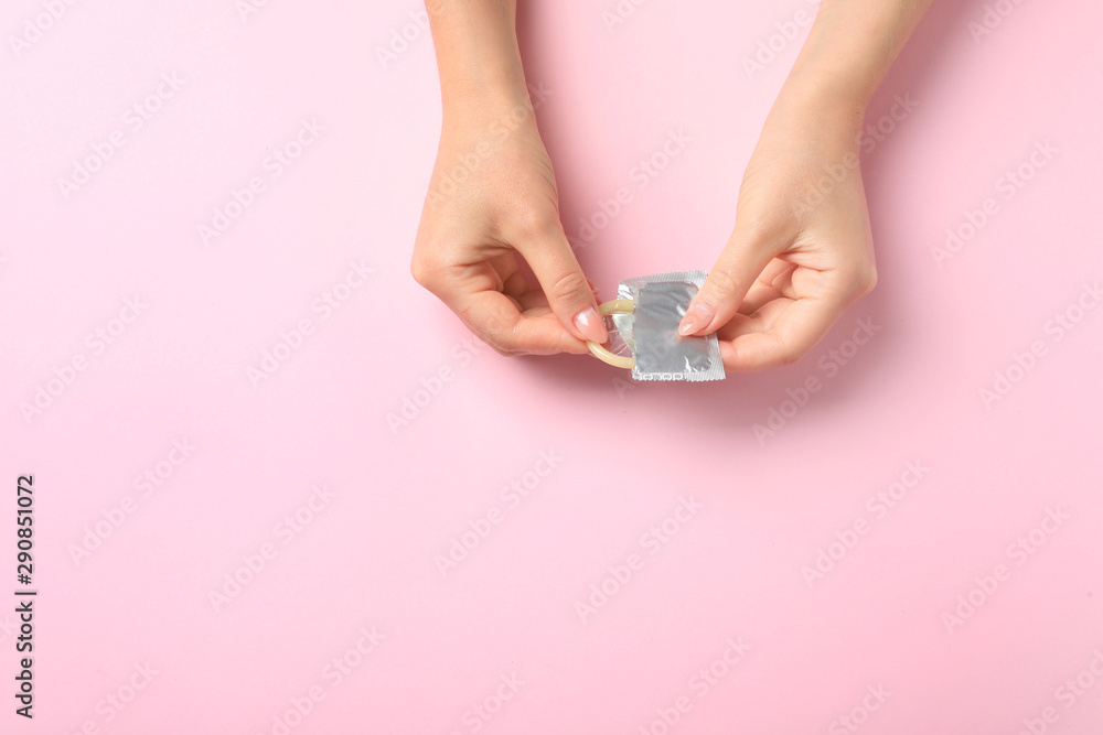 Fototapety, obrazy: Young woman with condom on pink background, top view with space for text. Safe sex