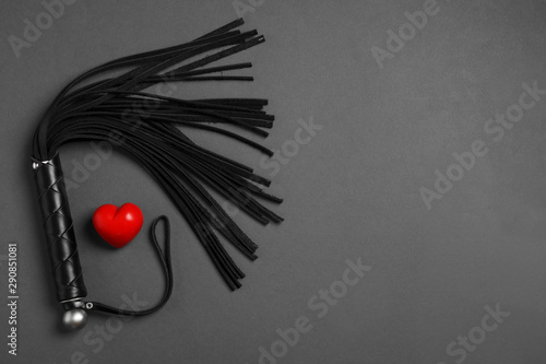Fototapeta Black whip and red heart on dark background, flat lay with space for text. Sexual role play accessory obraz