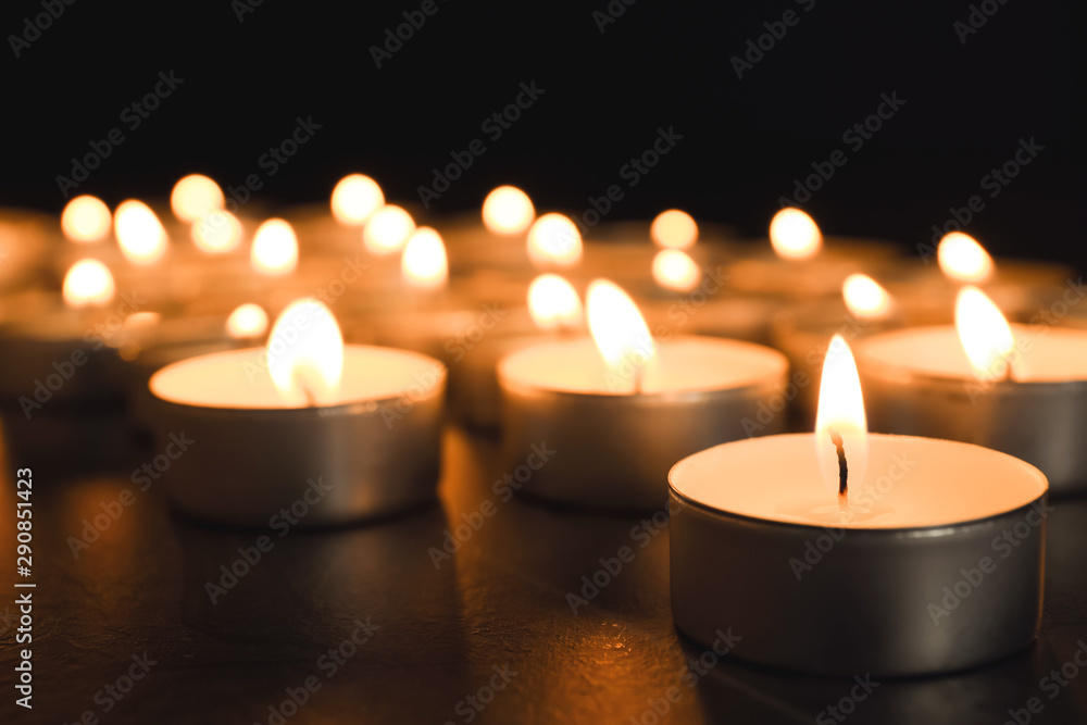 Fototapeta Burning candles on table in darkness, closeup. Funeral symbol