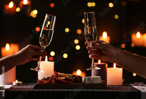 Fotografía Young couple with glasses of champagne having romantic candlelight dinner at tab