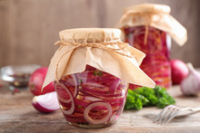 Jars Of Pickled Onions On Wooden Table