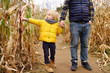 Family walking among the dried corn stalks in a corn maze.