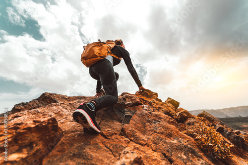 Fényképezés Success woman hiker hiking on sunrise mountain peak - Young woman with backpack rise to the mountain top