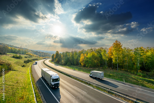 Vászonkép Trucks driving on the asphalt highway between deciduous forest in autumn colors under the radiant sun and dramatic clouds