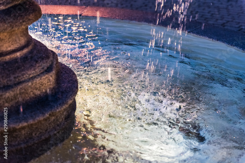 Closeup of splashing water fountain in downtown village park during evening dark night with illuminated light lamps - 290860825