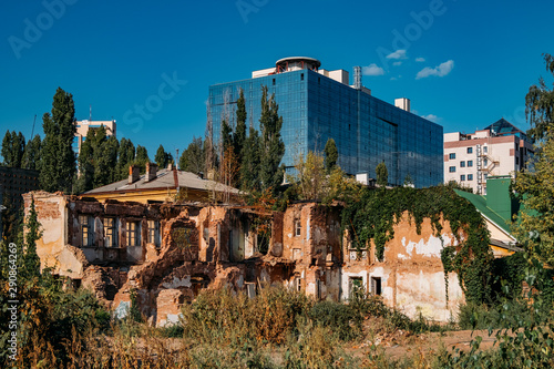 Obraz na plátně Old abandoned overgrown ruined house on modern building   background, Voronezh, Russia