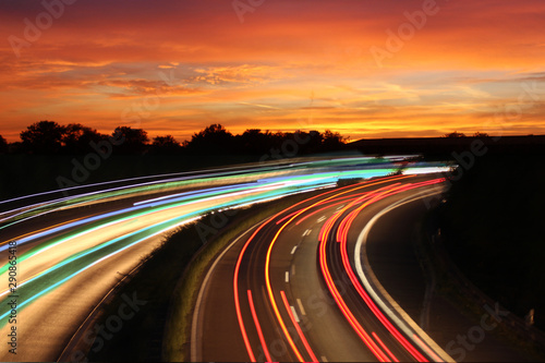Foto auf Leinwand Rotglühen Traffic with motion cars with luminous speed lines and evening sky with beautiful sunset sky, natural landscape