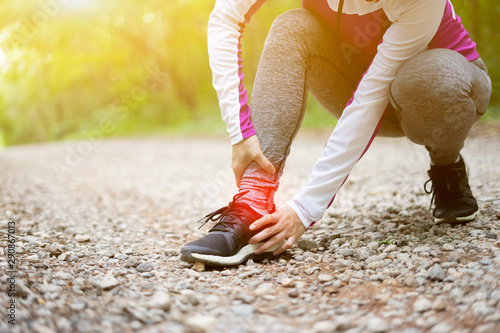 sport runner woman cramps in leg and feel pain, athletic young Asian girl in sportswear touching her muscles ankle painful injury outside after exercise workout in nature road Wallpaper Mural