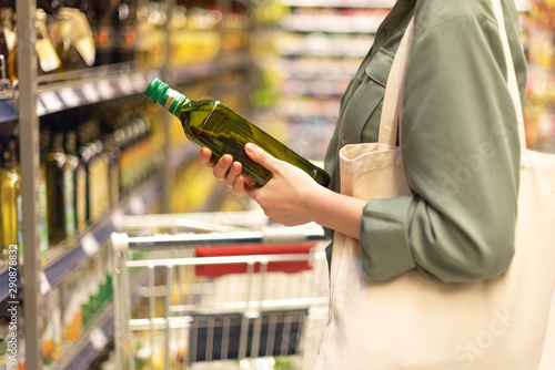 Fototapeta Girl choosing bottle of oil in grocery section of supermarket. Copy space. Healthy diet concept. Sustainable lifestyle. obraz