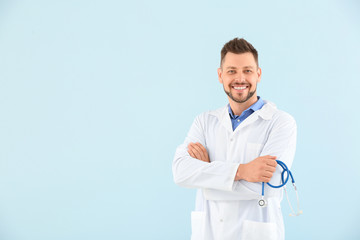 Male doctor with stethoscope on light color background