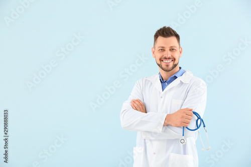 Fotomural  Male doctor with stethoscope on light color background
