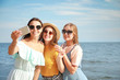 Happy young women taking selfie on sea beach at resort