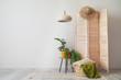 Leinwanddruck Bild Wooden folding screen with plants on table and wicker basket near light wall in living room