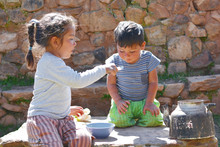 Little Latin Children Sitting On The Big Stone And Eating From A Bowl.
