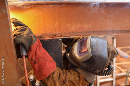 Fotografie, Tablou  Macro pic of maintenance welder wearing red safety glove welding helmet with pow