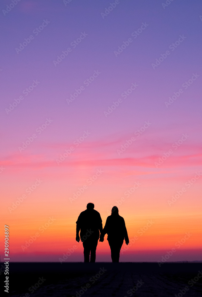 Fototapety, obrazy: silhouette of man and woman walk holding hands in colorful sunset
