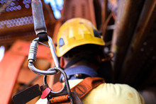 Construction Worker Welder Wearing Safety Helmet, Fall Arrest Harness Clipping Locking Karabiner Attached Retraceable Energy Shock Absorber Lanyard Device On The Back Of His Safety Harness Loop