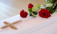 A White Coffin With Red Roses And A Sand Cross After Blessing