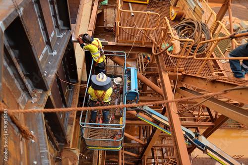 Maintenance welder on Elevating Work Platform wearing fall arrest safety harness Fototapeta