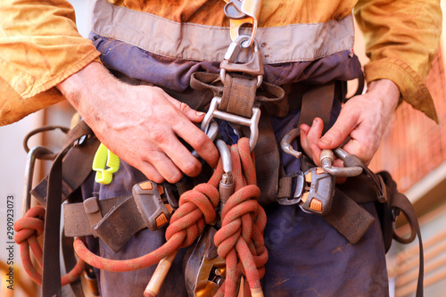 Closeup picture of male rope access worker hand wearing full safety harness clip Canvas Print