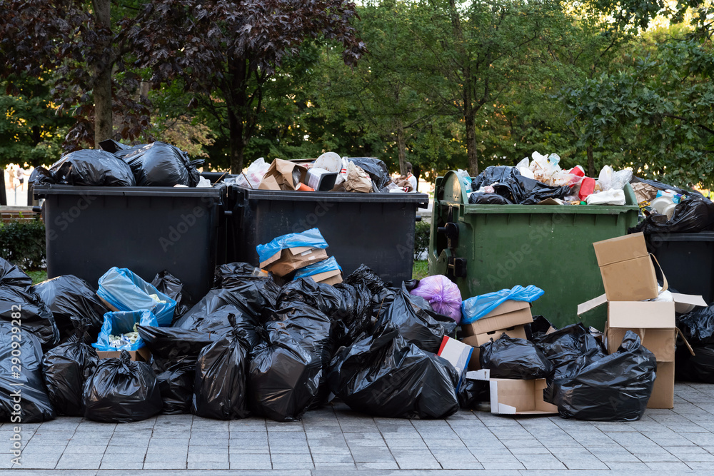 Huge garbage piles next to the dumpster after city fair. Stacks of litter bags overflow trash cans after festival in a city