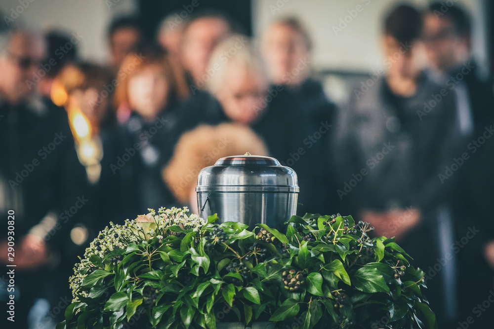 Fototapeta A metal urn with ashes of a dead person on a funeral, with people mourning in the background on a memorial service. Sad grieving moment at the end of a life. Last farewell to a person in an urn.