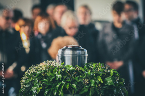 Canvas Print A metal urn with ashes of a dead person on a funeral, with people mourning in the background on a memorial service