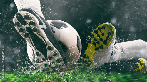 Obraz Football scene at night match with close up of a soccer shoe hitting the ball with power - fototapety do salonu