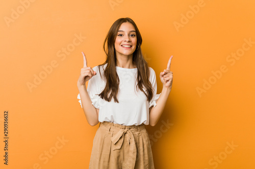 Fotografía  Young caucasian woman indicates with both fore fingers up showing a blank space